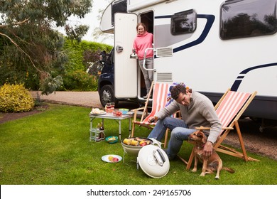 Couple In Van Enjoying Barbeque On Camping Holiday