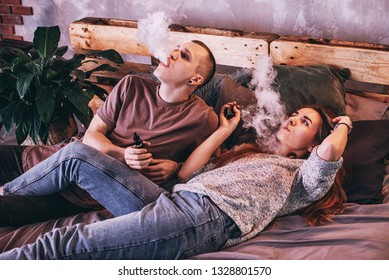 Couple vaping. Young man and woman blowing smoke while sitting on a wooden bed. The concept of relationships and vape dependence with copy space