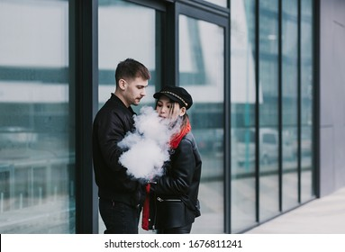 Couple vaping. Young man and woman blowing smoke in city. Relationship and vape addiction concept with copy space.