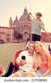 Couple in Venice doing Gondola ride on canal grande taking selfie self portrait using smartphone camera. Happy young romantic couple traveling in Italy, Europe on vacation holidays.