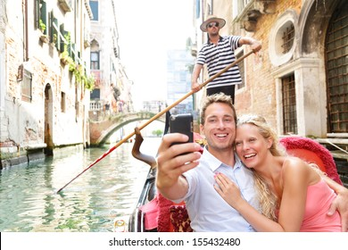 Couple in Venice on Gondola ride romance in boat happy together on travel vacation holidays. Romantic young beautiful couple taking self-portrait sailing in Venetian canal in gondola. Italy.