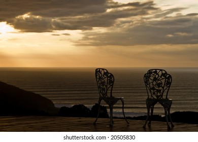 A couple of vintage chairs with a great sunset view