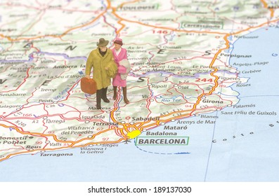 A couple of vintage small figures walking in a map to Barcelona destination, selective focus.