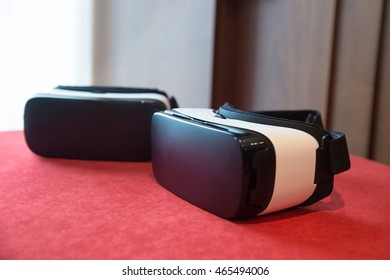Couple of virtual reality headsets, laying on the table, prepared to be used. Advanced computer technology and VR experience concept.