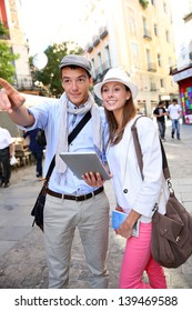 Couple visiting Madrid with help of digital tablet