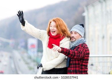 Couple wag to air. Red hair woman wag from the bridge. Happy lady with guy welcomes to friends. Man in winter hat points by finger. Happy family loves travel.