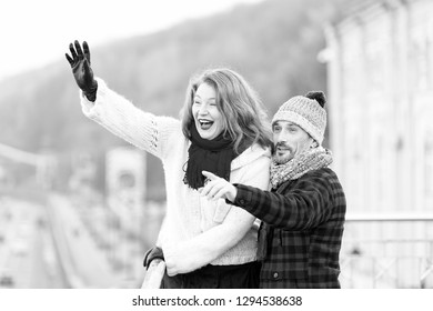 Couple wag to air. Red hair woman wag from the bridge. Happy lady with guy welcomes to friends. Men in winter hat points by finger. Happy family loves travel.