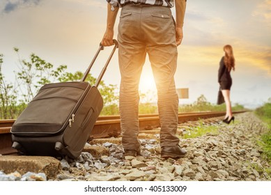 A couple waiting for the train at a railroad track