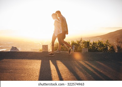 Couple walk along road at sunrise. Couple talking a walk on hillside road with bright sunlight.