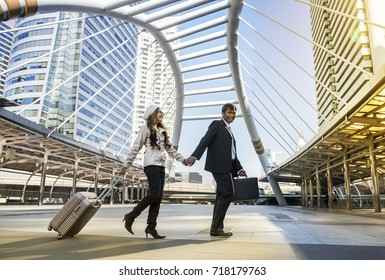 The couple walked on street hand in hand.The woman came back from oversea after finished work. She work at oversea company. She flight over night and cross the sea to visited her husband every month.