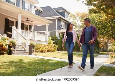 Couple Walking Along Suburban Street Holding Hands