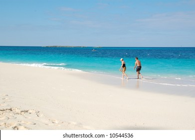 Couple walking along the water line on the beach