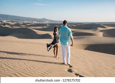 couple walking at the beach of Maspalomas Gran Canaria Spain, men and woman at the sand dunes desert of Maspalomas