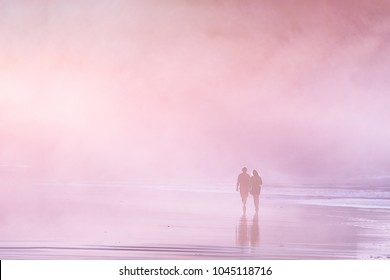 Couple walking in the beach at the sunset. Vintage effect