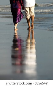 Couple walking by the seaside with reflected image on the sand