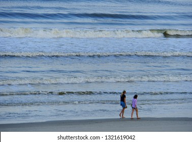 A couple walking by the shore at New Smyrna Beach, Florida, U.S.A