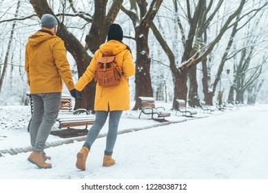 couple walking by snowed city park talking socializing. romantic date in winter time