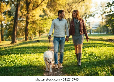 Couple walking the dog together in the park.