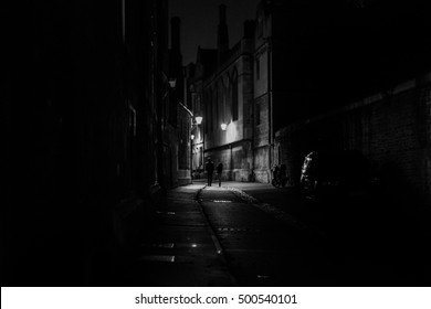 A couple walking down a dark alley in black and white