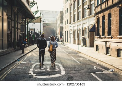 A couple walking down a london street while the suns falls. Warm tones and a sense of love predominates in this photo
