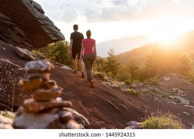 Couple walking down a mountain trail at sunset.