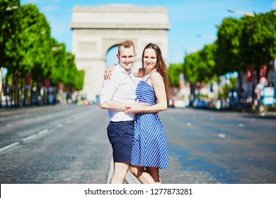 Couple walking in front of Triumphal arch in Paris, France