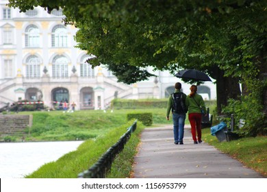 Couple walking in garden of Nymphenburg Castle in Munich, Germany