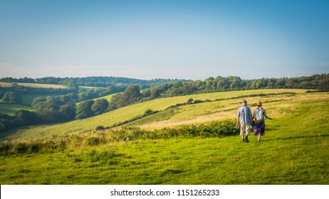 A couple is walking with German Shepherd dog on a coastal pathway in the green British countryside on hills on a hot summer day near Sidmouth, Devon, United Kingdom, UK. Jurassic Coast landscape.