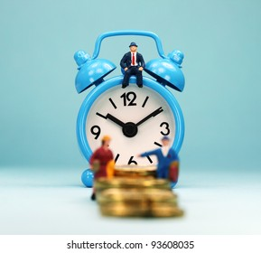 A couple walking up a golden coin stairway, with the bank manager ahead of them sat on a pastel blue alarm clock, asking the question, can you last the financial journey.