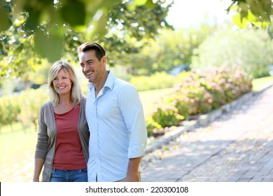 Couple walking hand in hand in park