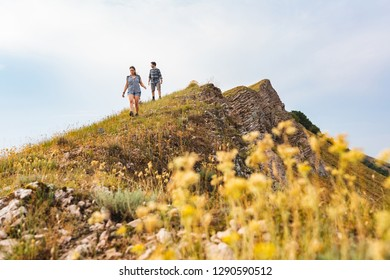Couple walking and hiking at mountains in spring. Outdoor leisure activity on top of a mountain. Flower on foreground and people on background.