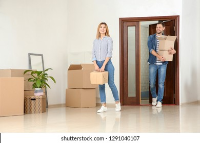 Couple walking into their new house with moving boxes