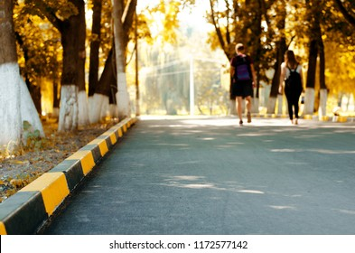 Couple walking on asphalt road and concrete sidewalk yellow and black curb. Autumn park