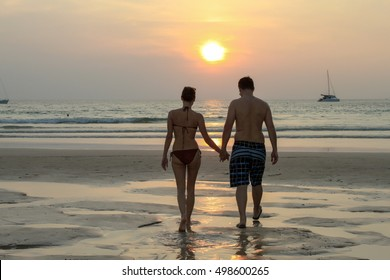 couple walking on beach at the sunset