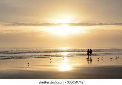 Couple walking on beautiful foggy beach at sunrise, Daytona Beach, Florida.
