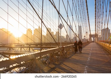 Couple walking on pedestrian path across Brooklyn bridge. New York City Manhattan downtown skyline in sunset with skyscrapers illuminated over East River panorama as seen from Brooklyn bridge.