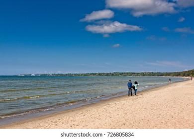 A couple walking on the Pirita beach at Tallinn, Estonia. The Baltic Sea beach is very popular in the summertime.