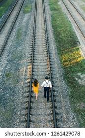 Couple walking on rails during sunset