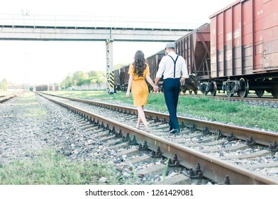 Couple walking on rails during sunset