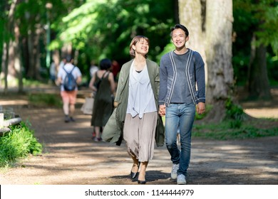 Couple walking on a refreshing path of fresh green on a date