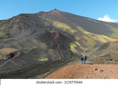 couple walking on summit Etna Volcano, Sicily