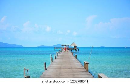 Couple Walking on Wooden Pier Among Blue Sea
