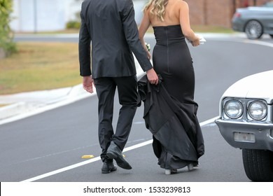 A couple walking to their car in formal wear both in black.
