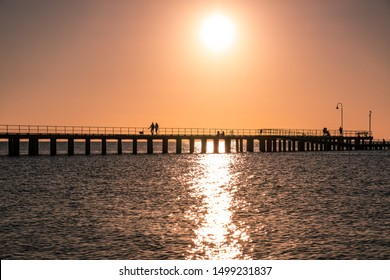 Couple walking their dog on a pier silhouettes at sunset