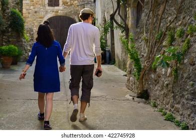 Couple walking through little alley, Aiguèze, France
