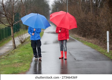 A couple is walking through the rain with umbrellas and rain cloth.