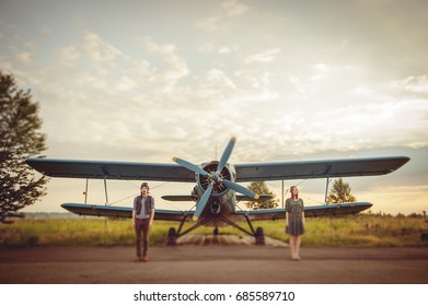 Couple walking together  with airplane on background at sunset