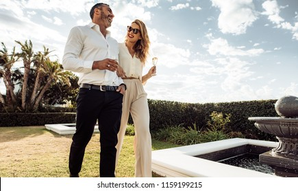 Couple walking together with wine in lawn of their house. Man and woman with a drink walking outdoors and having fun.