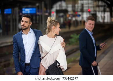 couple walking at train station and woman flirting with another man