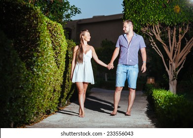 couple walking in tropical resort park at sunset. Happy couple on vacation
